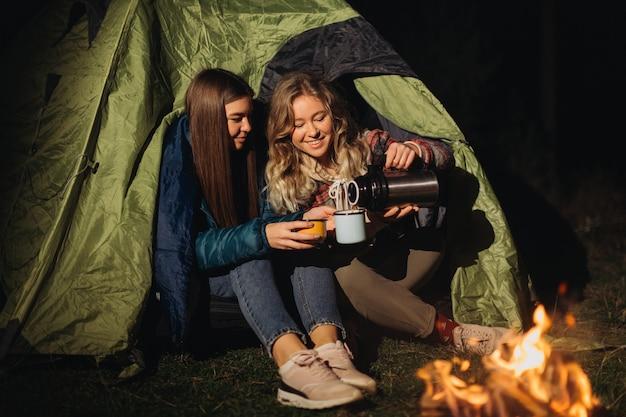 テントに座って夜にお茶を飲む女友達 Premium写真