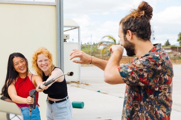 Female friends splashing water on protecting man at car wash Free Photo