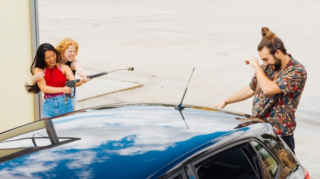 Female friends splattering water on male behind car Free Photo