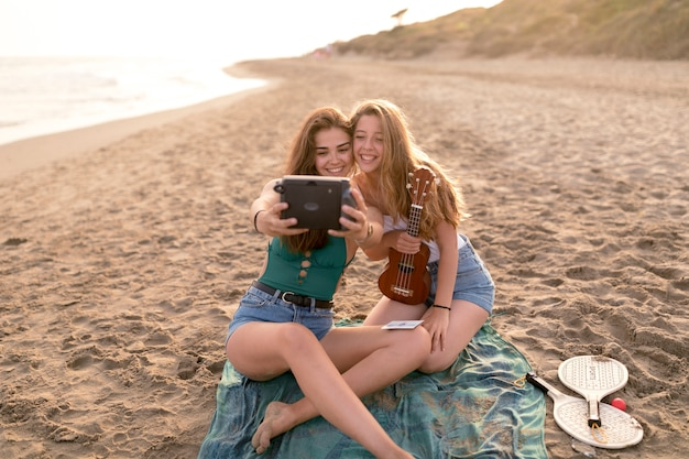 Female friends taking self portrait from instant camera at scenics beach Free Photo