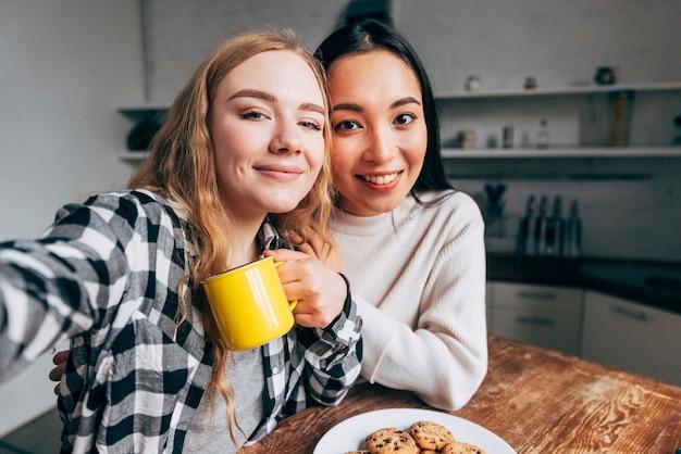 Female friends taking selfie in kitchen Free Photo