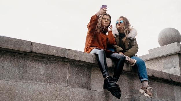 屋外で自分撮りをしている女性の友人 無料写真