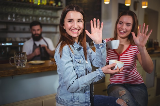 Female friends waving hands while having a cup of coffee Free Photo