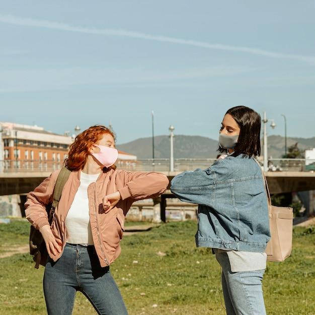 Amici femminili con maschere facciali all'aperto facendo il saluto di gomito Foto Gratuite