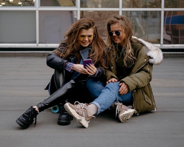 Amici femminili con lo smartphone divertendosi insieme all'aperto Foto Gratuite