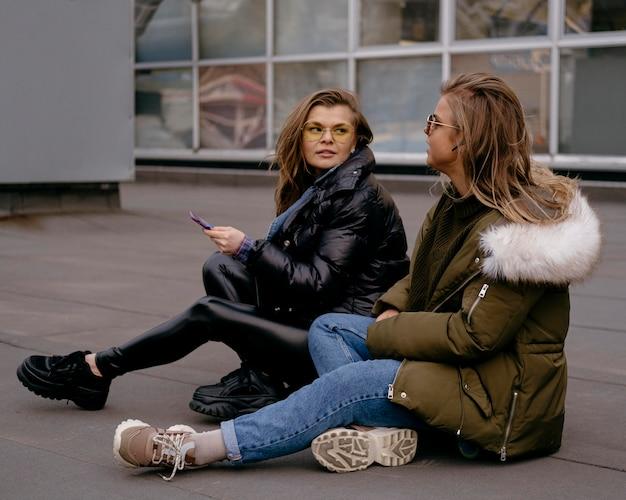 Amici femminili con lo smartphone all'aperto insieme Foto Gratuite