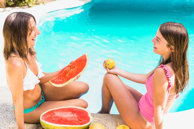 Female friends with tropical fruits near pool Free Photo