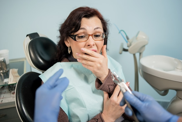Female frightened by dentists and covering her mouth with hand at the dentist appointment in the dental clinic Premium Photo