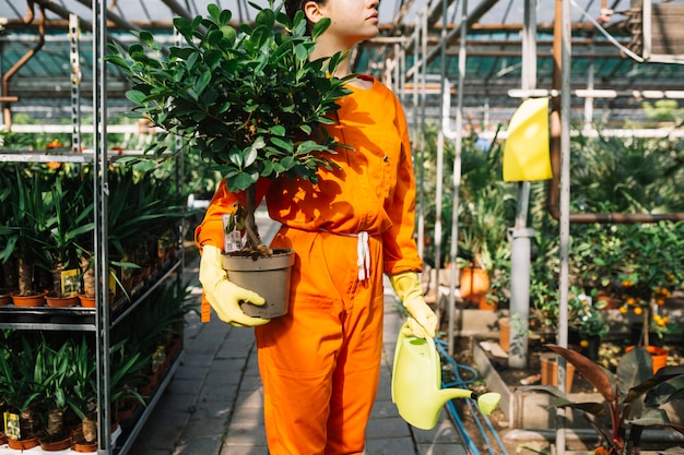 Female gardener holding potted plant and watering can Free Photo