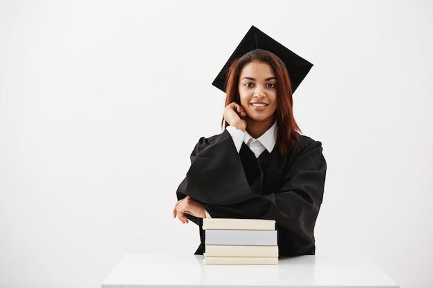 キャップとマントルの白い表面の上の本で座っている笑顔の女性卒業生 無料写真