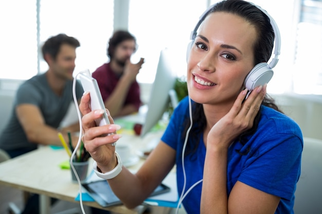Female graphic designer listening music from mobile phone Free Photo