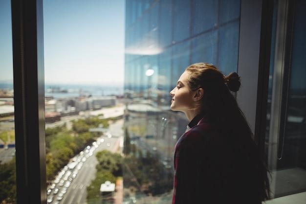 窓から見ている女性のグラフィックデザイナー Premium写真