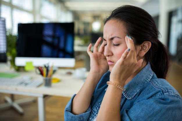 Female graphic designer suffering from head pain Free Photo