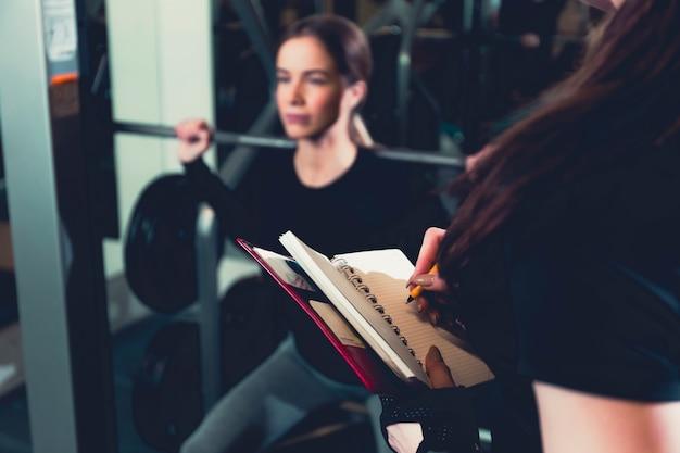 Female gym trainer writing on diary Free Photo