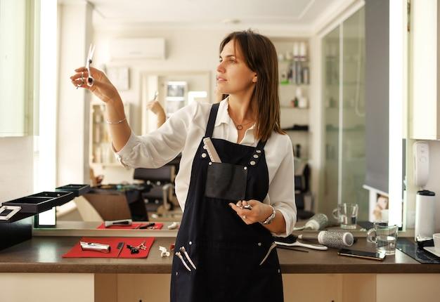 그녀의 직장, 미용실에서 여성 미용사. 앞치마의 스타일리스트는 장비, 헤어 살롱과 함께 포즈를 취합니다. 뷰티 사업, 전문 서비스 프리미엄 사진