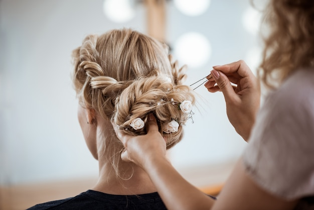 Female hairdresser making hairstyle to blonde woman in beauty salon Free Photo