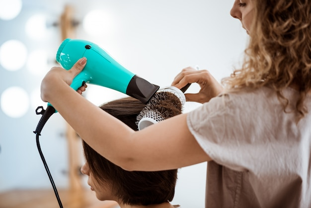 Female hairdresser making hairstyle to brunette woman in beauty salon Free Photo