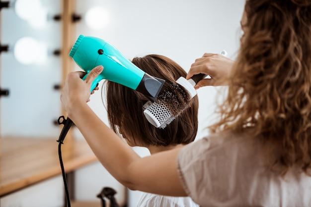 뷰티 살롱에서 갈색 머리 여자 헤어 스타일을 만드는 여성 미용사 무료 사진
