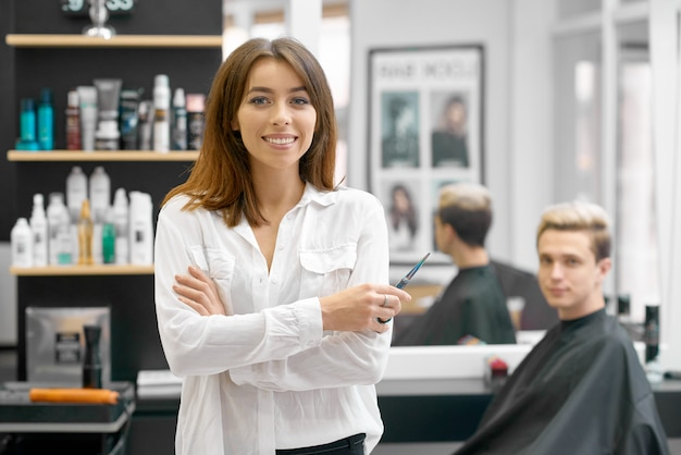 Female hairdresser posing in front of young male client. Premium Photo