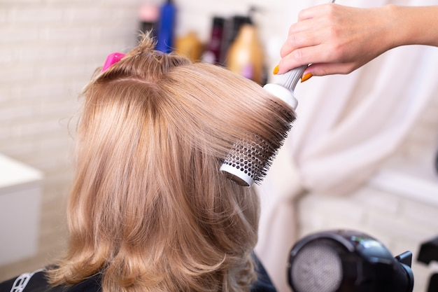 Female hairdresser's hand brushing and blow drying blonde  hair in beauty salon Premium Photo