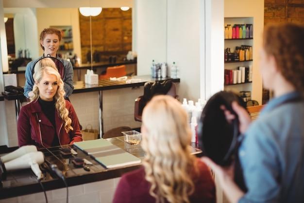 クライアントの髪をスタイリングする女性の美容師 無料写真