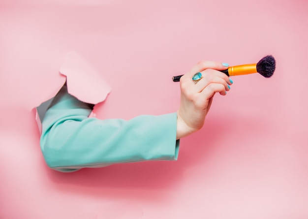 Female hand in classic blue jacket with visage brush Premium Photo