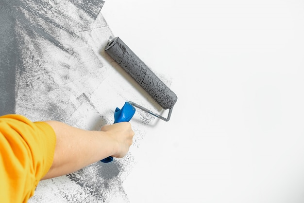 女性の手のクローズアップは、灰色で壁をペイントします。修理、変更、デザイン、背景の概念 Premium写真