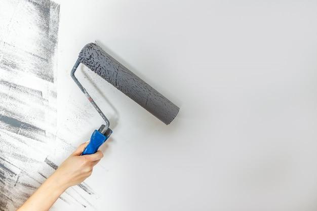 女性の手のクローズアップは、灰色で壁をペイントします。修理、変更、設計の概念 Premium写真
