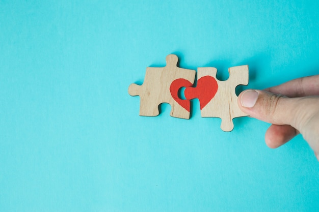 Female hand connecting puzzle with drawn red heart on blue background. love . st. valentine day. reconciliation. Premium Photo