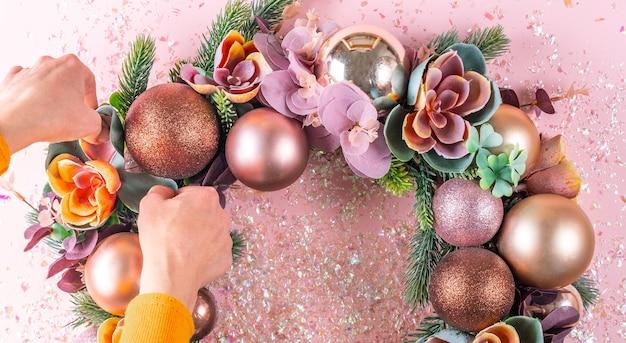 Женская рука украшает красивый необычный рождественский венок Premium Фотографии