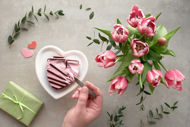 Female hand dipping a spoon in pink heart ice cream and pink tulips Premium Photo