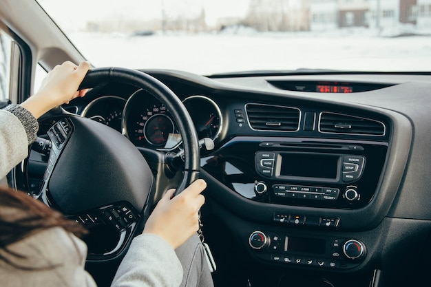 Female hand on the driving wheels. driving a modern car steering wheel and hand close-up Premium Photo