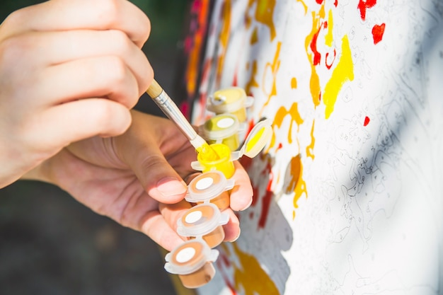 A female hand dunks a brush in yellow paint to draw on the canvas with numbers Premium Photo