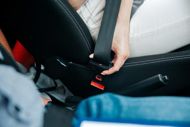 Female hand fastens seat belt. close-up cut view of woman in white jeans holding black seatbelt. road traffic safety concept. conscious driving concept. Premium Photo