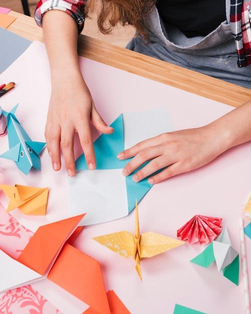 Female hand folding paper while making decorative origami art craft Free Photo