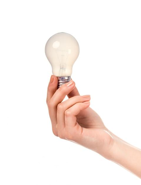 Женская рука держит лампочку Premium Фотографии