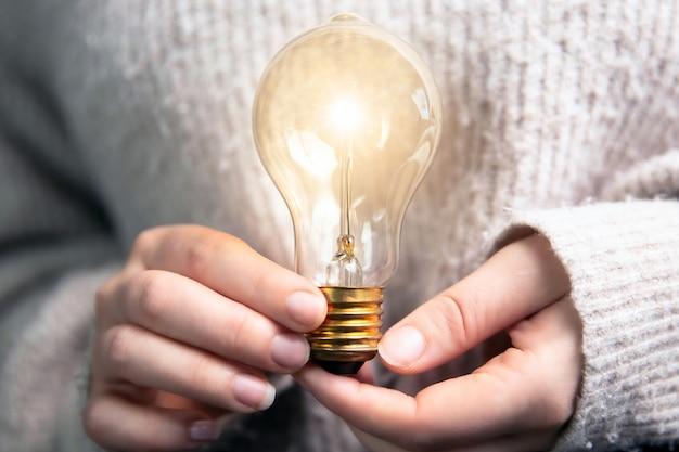 Женская рука, держащая сияющую лампочку Premium Фотографии