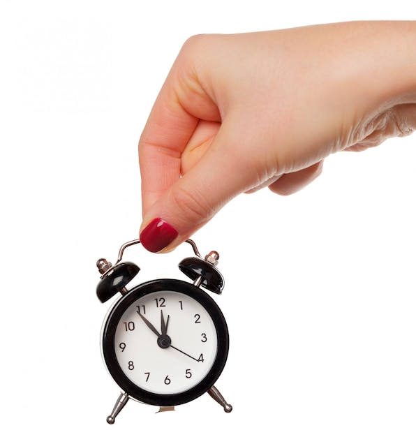 Female hand holding alarm clock on white Premium Photo