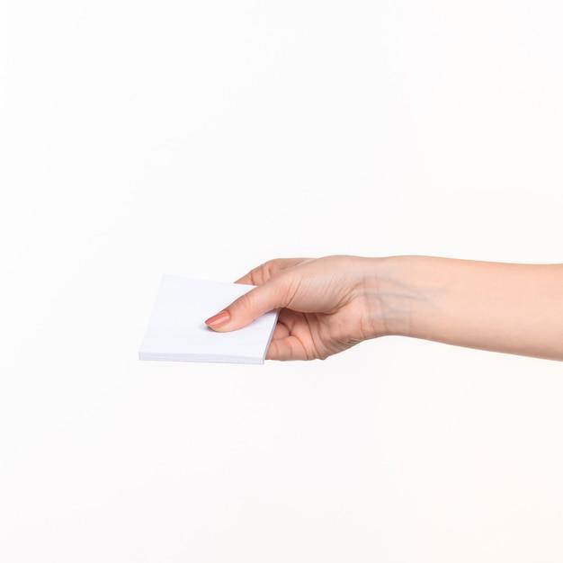 Женская рука держит чистый лист бумаги для записей на белом фоне с правой тенью Бесплатные Фотографии
