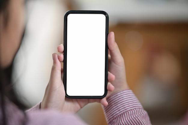 Female hand holding blank white screen mobile phone over blurred bokeh background Premium Photo