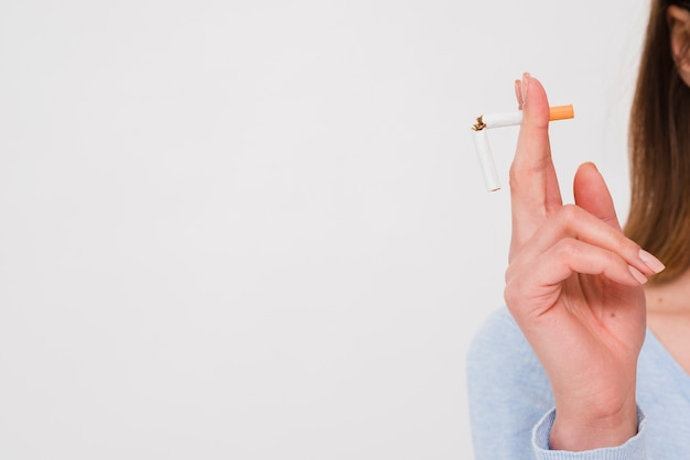 Female hand holding broken cigarette isolated on white backdrop Free Photo