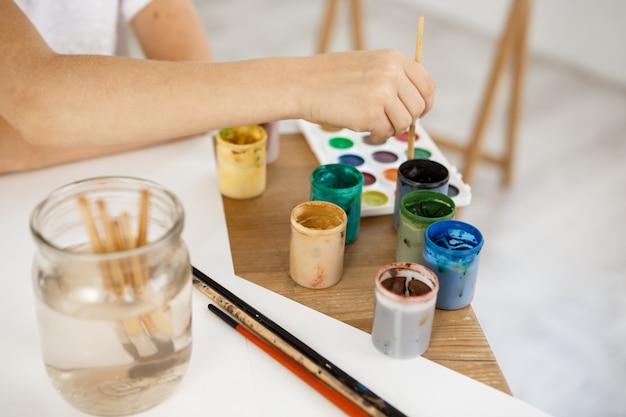 Женская рука держа кисть и углубляя его в краску. kid живопись с использованием акварели во время урока в художественной комнате. Бесплатные Фотографии