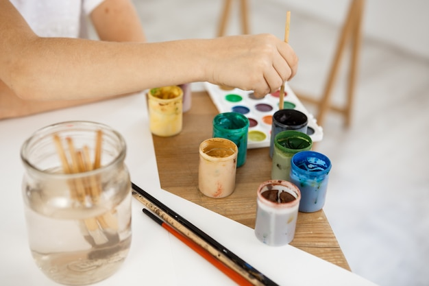 Female hand holding brush and deeping it into paint. kid painting using watercolour during lesson in the art room. Free Photo