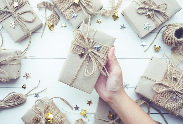 Female hand holding christmas presents gift box collection in vintage style Premium Photo