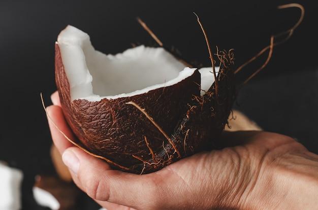 Female hand holding a coconut half on black Premium Photo
