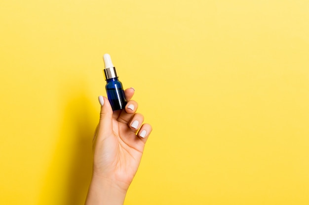 Female hand holding cream bottle of lotion isolated. girl give tube cosmetic products on yellow background Premium Photo