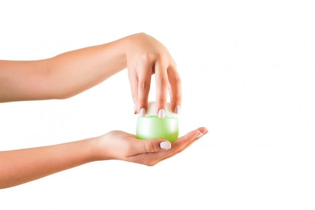 Female hand holding cream bottle of lotion isolated Premium Photo