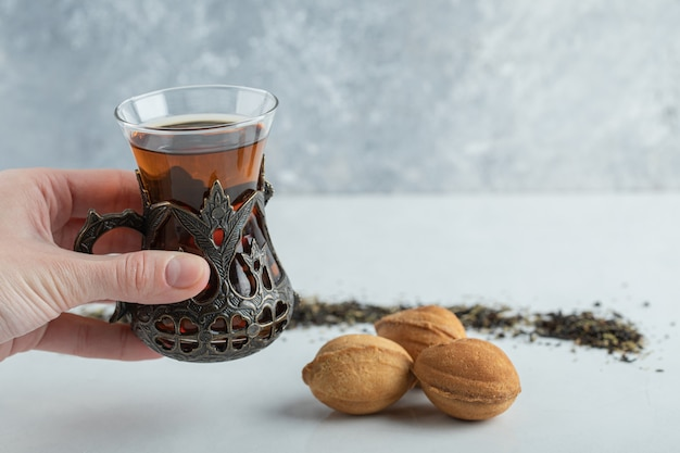 Female hand holding a cup of herbal tea with sweet walnut shaped cookie. Free Photo