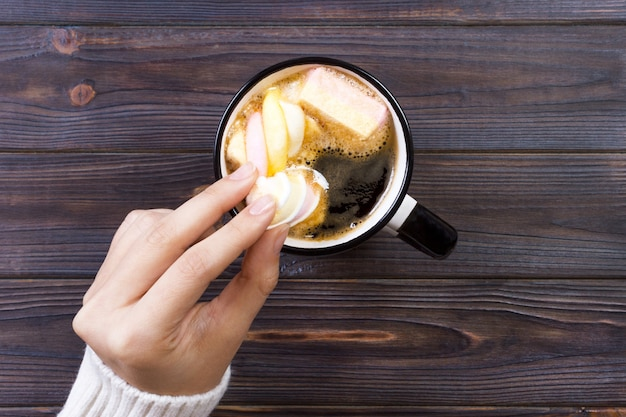 Female hand holding cup of hot cocoa or chocolate with marshmallow on wooden table from above Premium Photo