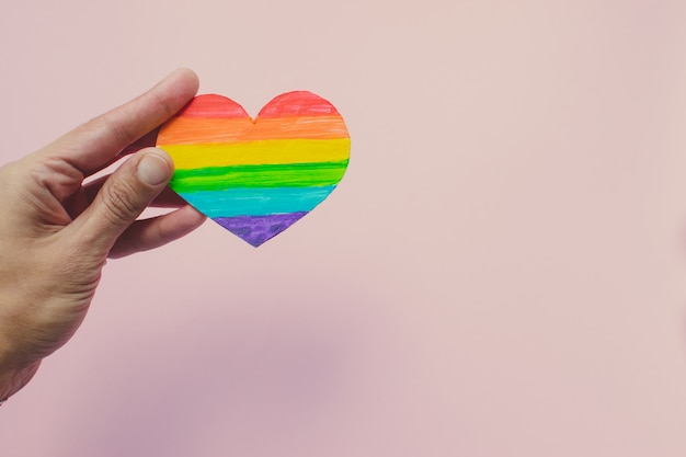 Female hand holding decorative heart with rainbow stripes on pink background. lgbt pride flag, human rights. Premium Photo